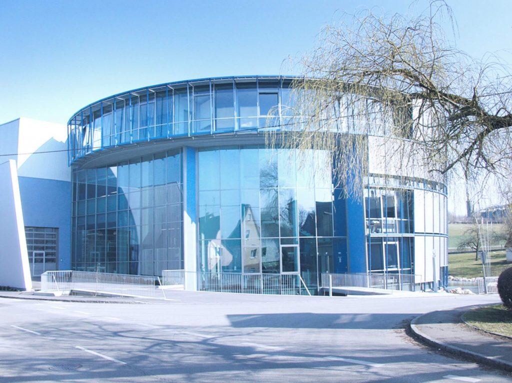 Frontansicht des neu erbauten Gebäudes, das halbrund ist und eine Glasfassade hat. Der Neubau ist als Zentrale für die übergreifenden Abteilungen gebaut worden.