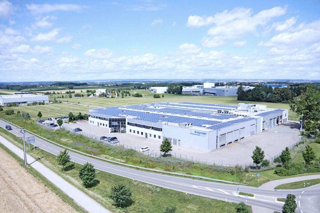 Luftaufnahme des Standortes in Laupheim, dessen Produktionsfläche verdoppelt wurde. Auf dem Dach der Fertigungshalle befinden sich Photovoltaik-Anlagen.