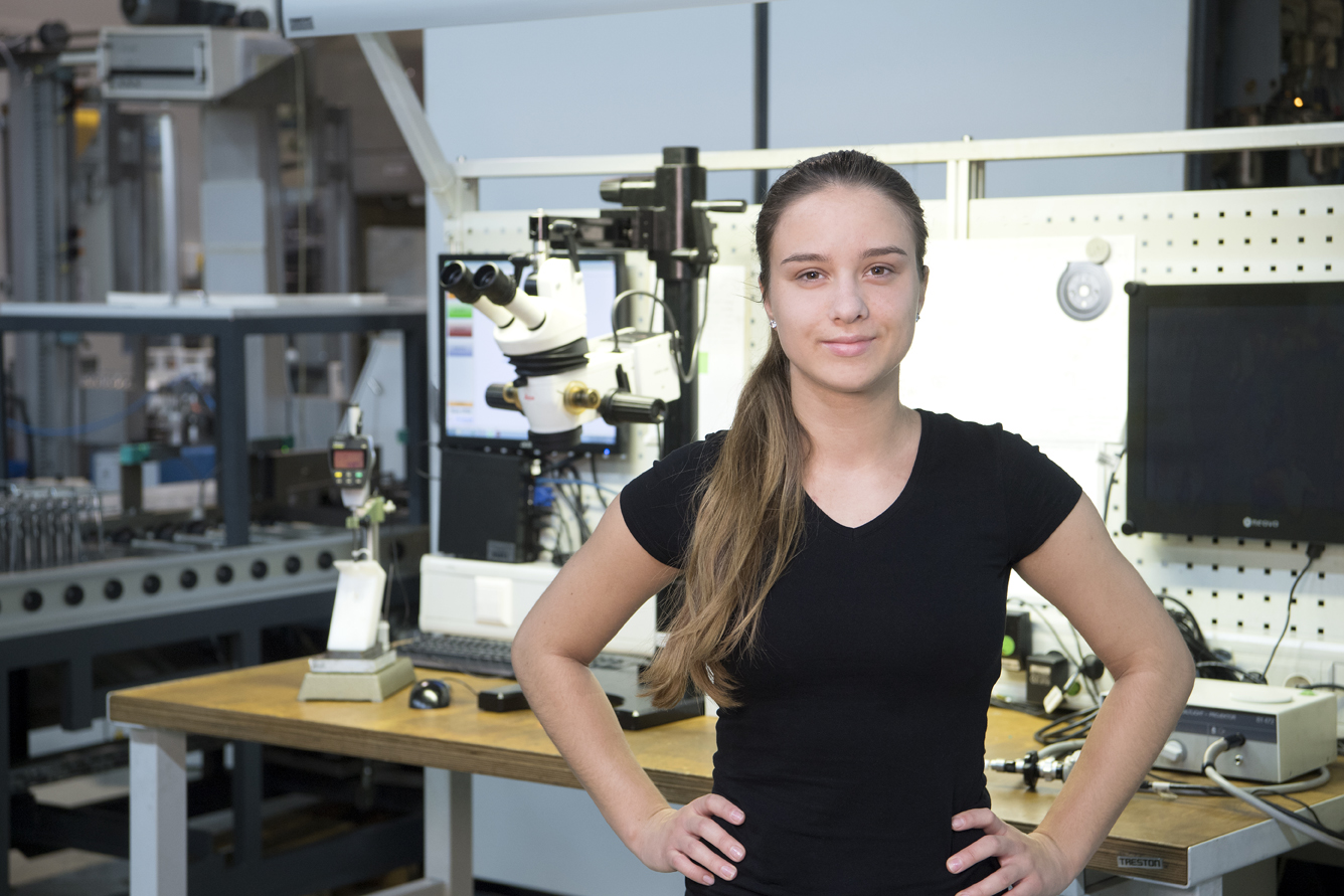 Young Woman with brown hair and hands in her hips stands in front of a technoscope