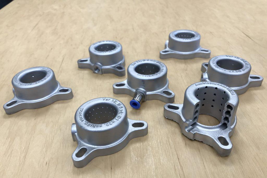Sieben additiv gefertigte Ausblastunnel für CNC-Maschinen liegen auf einem Tisch. Ein Ausblastunnel ist zu einem Viertel aufgeschnitten, um die Luftbahnen besser sehen zu können