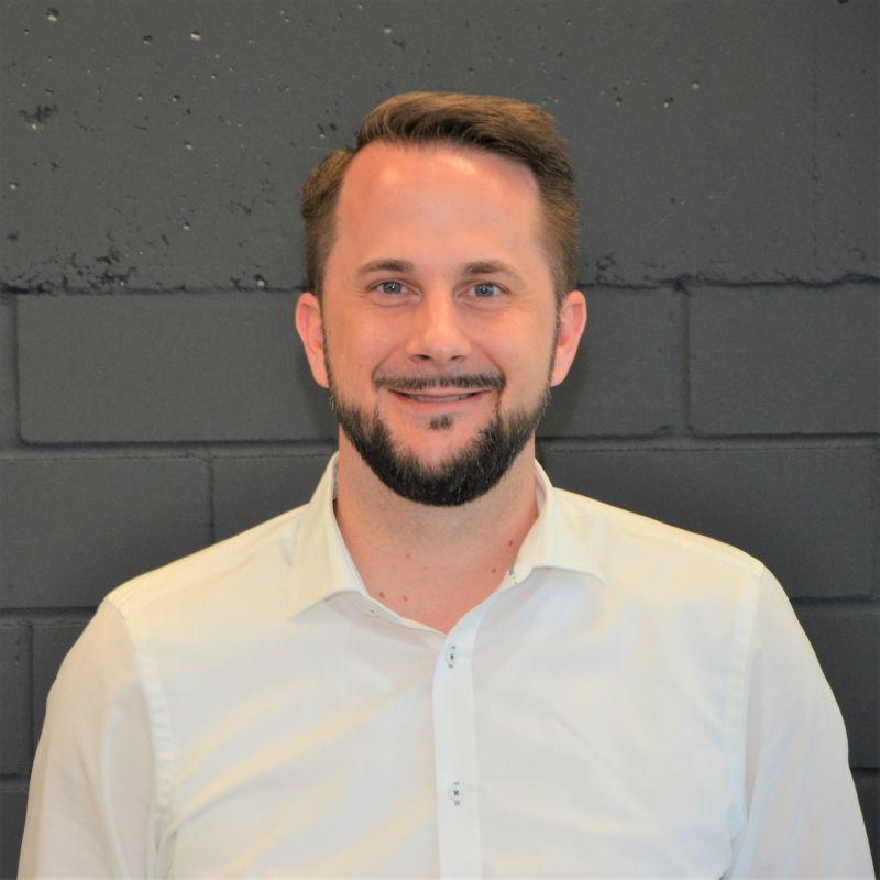 Junger braunhaariger Herr mit Vollbart in weißem Hemd steht vor einer grauen Wand.
