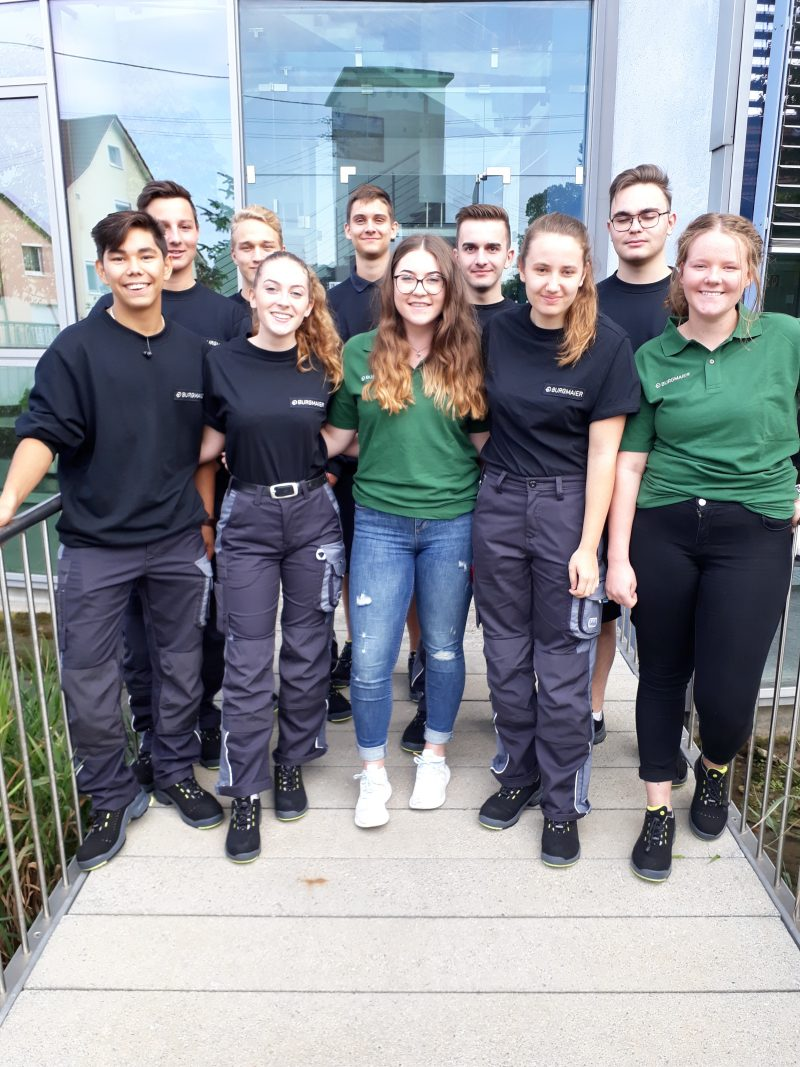 Die 10 neuen Auszubildenden der Firma Burgmaier stehen auf der Brücke vor dem Hauptgebäude in Allmendingen.